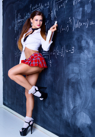 attractive striptease dancer dressed as a schoolgirl against a chalkboard in the classroom 스톡 콘텐츠