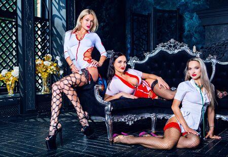 trois belles danseuses de strip-tease habillées en infirmière en studio Banque d'images