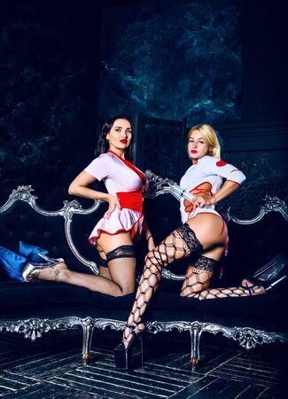 twee mooie striptease danseressen verkleed als verpleegster in de studio