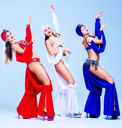 beautiful sexy women wearing  stage costumes of a belly-dancers, in the studio