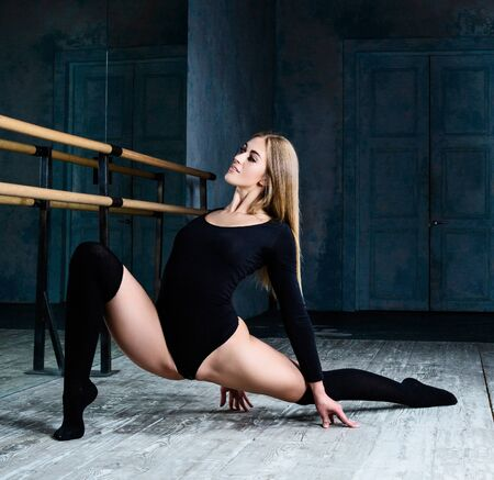 beautiful young blond woman ballet dancer doing exercise at  dance class near the barre indoors