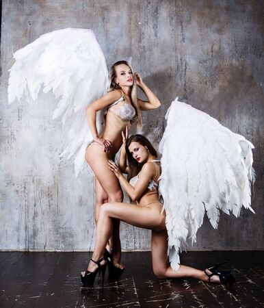 beautiful young models wearing white angel wings in the studio