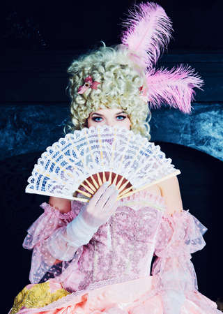 Indoors shot of a beautiful young woman in the Marie Antoinette style in the palace