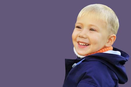 Happy smiling boy in autumn jacket on monophonic background Stock fotó