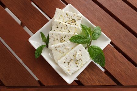 queso fresco blanco: queso feta griego en un plato blanco con orégano y menta