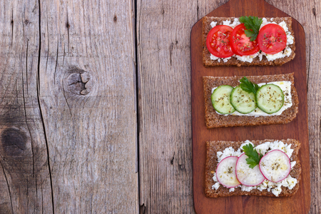 black bread: Black bread with feta cheese tomato,cucumber and radish on cutting board