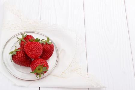 白い木製のテーブル、食べ物の背景にイチゴ