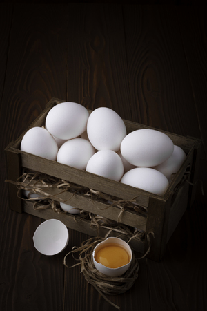 wooden crate: Bunch of fresh white eggs in a wooden crate on a brown background