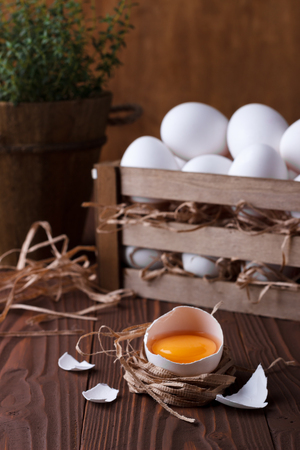 wooden crate: Closeup of an broken egg on wooden background with a bunch of eggs in a wooden crate Stock Photo