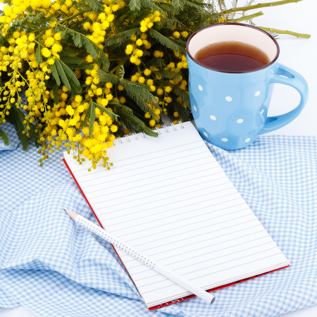 eight note: Mimosa flowers, notepad and cup of tea on a blue cloth,