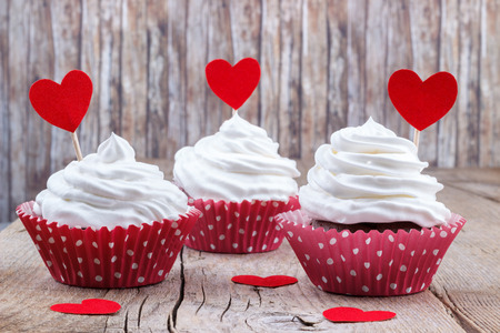 Cupcakes with white buttercream frosting on  wooden table with a paper hearts