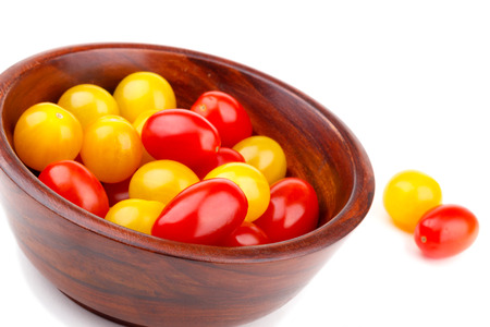 bawl: Yellow and red tomato cherry in wooden bawl isolated on white