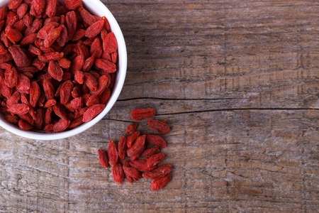 bawl: Goji berries in a white  bawl on old wooden board Stock Photo
