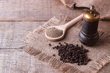grounds: Black pepper corns and Black pepper Powder on wooden background