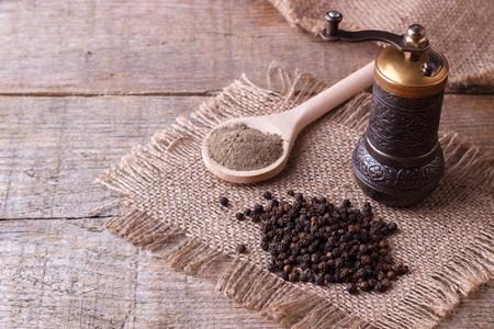 Zwarte peperkorrels en zwarte peper poeder op houten achtergrond