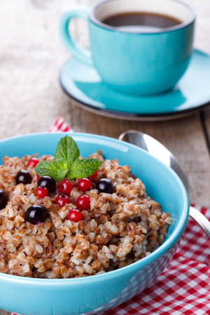 bawl: Buckwheat porridge in a bowl with red currant and blueberries,selective focus Stock Photo