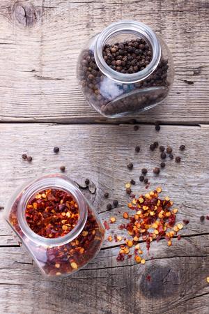 chiles secos: hojuelas de chile y pimienta negro en frascos en el fondo de madera Foto de archivo
