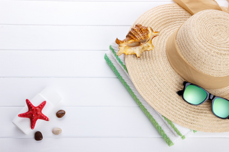 sunhat: Beach accessories on wooden background for summer or vacation concept. Sunhat, sunglasses beach towel, sunburn lotion. Space for text. Stock Photo
