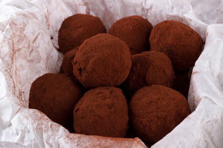 Homemade chocolate rum balls with cocoa powder in parchment paper Stockfoto