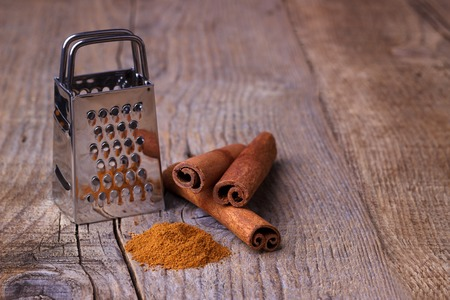 grater: Cinnamon sticks, powder and grater on rustic wooden background Stock Photo