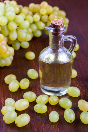 grape seed: Grape seed oil in a glass jar on wooden background