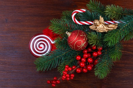 Christmas background with fir branches,berries and decoration on old wooden board Stock Photo