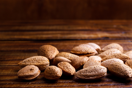 kernel: Sweet almonds with kernel on wooden board Stock Photo