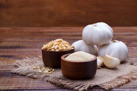 knoflookteentjes, bol, vlokken en poeder op oud houten bord