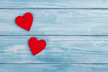 Two red wooden hearts on a blue vintage wooden background Stock Photo
