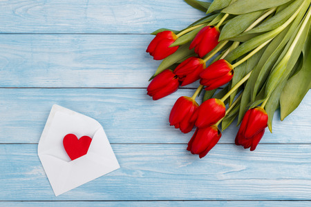 bunch of hearts: Red tulips and envelope wit heart on blue wooden table. Top view with copy space.Valentines day