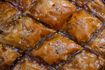 Homemade baklava with nuts and honey syrup on old rustic wooden table