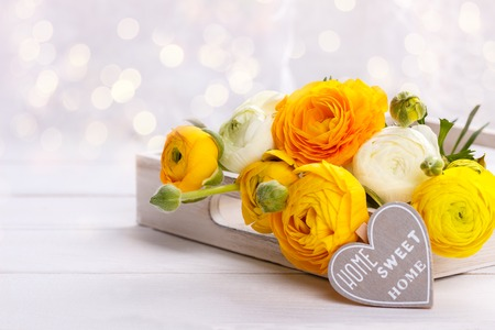 Close up of a bouquet of yellow ranunculus and a wooden heart with message Home sweet home Stock Photo