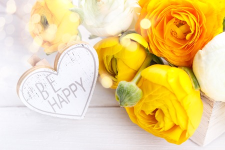 Close up of a bouquet of yellow ranunculus and a wooden heart with message Be Happy