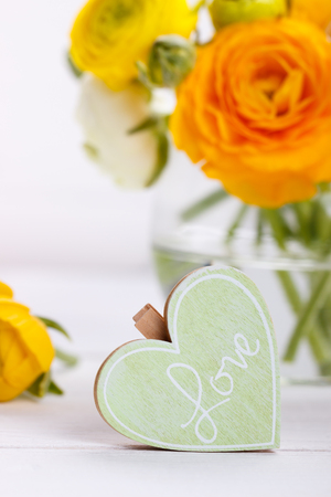 Wooden heart with message Love and bouquet of ranunculus Stock Photo