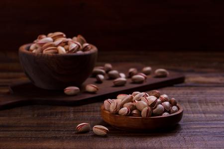 Pistachio nuts in wooden bowl, closeup,selective focus Stock Photo
