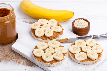 Rice cakes with peanut butter and slices of banana and sesame seeds on white wooden table Stock Photo