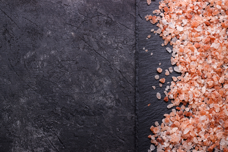 Pink himalayan salt over black slate stone, close up top view with space for text