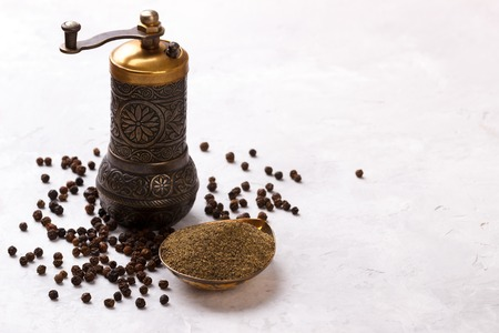 Black pepper corns,powder and old vintage mill on white stone background, top view Banco de Imagens