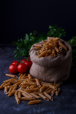 whole grain dried pasta for healthy eating, low key ,dark background Stock Photo