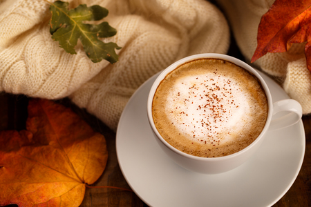 Hot coffee cappucino, blanket and autumn leaves on old wooden background. Seasonal relax concept Stock Photo