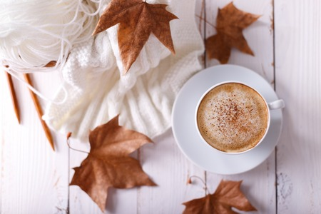 Hot coffee cappuccino, knitted blanket and autumn leaves on old wooden background. Seasonal relax concept