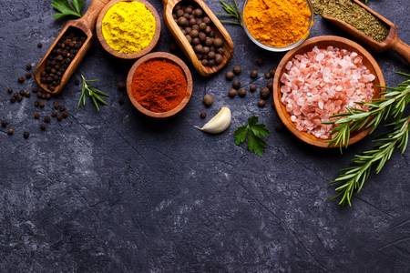 Spices and herbs over black stone background. Top view with free space for menu or recipes.
