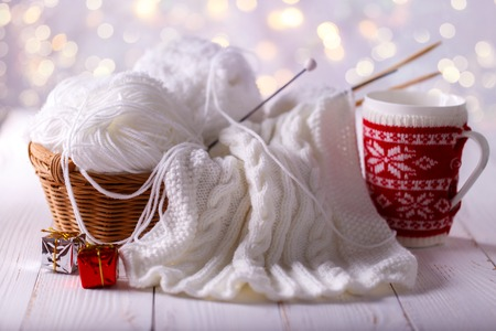 winter fashion: Balls of white yarn in a basket with knitting needles and cup of coffee on wooden background Stock Photo