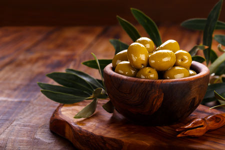 Green olives in olive wood bowl on old wooden background. Overhead view with space for text