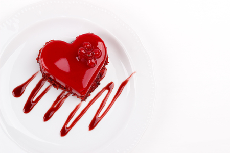 Heart shaped red velvet cake decorated with red currant on white plate, overhead view