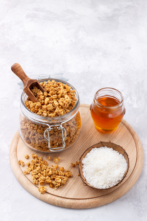 healthy breakfast with homemade oat and coconut granola in a jar on white background