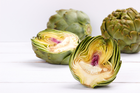 Ripe organic artichokes on white wooden table, copy space Stockfoto