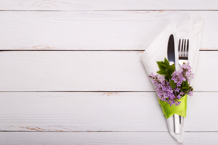 Spring festive table setting with vintage cutlery and lilac flowers on white wooden table,copy space flat lay