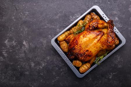 Pollo arrosto e patate su sfondo nero pietra ardesia, laici piatta con spazio di copia. Modello di menu o ricetta