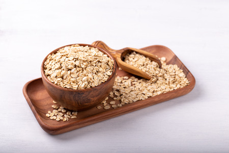 Old fashioned rolled oats in a wooden bowl on white wooden table